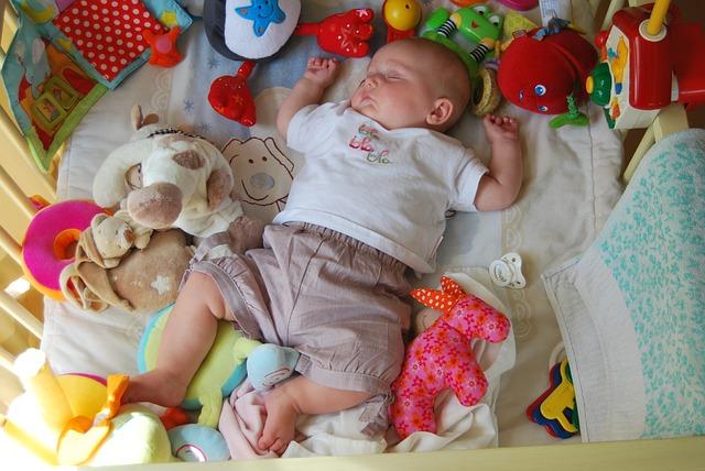 おもちゃに囲まれて眠る赤ちゃん