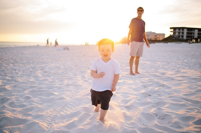 砂浜を走る子どもと見守る親